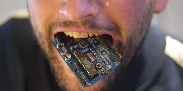 photo of man biting small circuit board