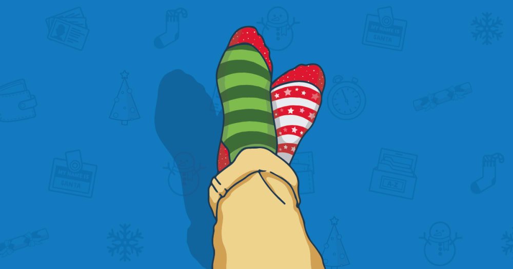 A pair of christmas socks are seen on a blue background